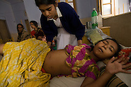 A nursing student assesses the condition of a young girl with a swollen abdomen at Kumudini Hospital in Narayanganj, Bangladesh.