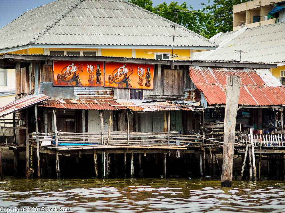 20 JULY 2015 - BANGKOK, THAILAND:   Dilapidated housing on the Chao Phraya River south of Pin Klao Bridge and the planned redevelopment of the riverfront. The Chao Phraya promenade is development project of parks, walkways and recreational areas on the Chao Phraya River between Pin Klao and Phra Nang Klao Bridges. The 14 kilometer long promenade will cost approximately 14 billion Baht (407 million US Dollars). The project involves the forced eviction of more than 200 communities of people who live along the river, a dozen riverfront  temples, several schools, and privately-owned piers on both sides of the Chao Phraya River. Construction is scheduled on the project is scheduled to start in early 2016. There has been very little public input on the planned redevelopment.         PHOTO BY JACK KURTZ