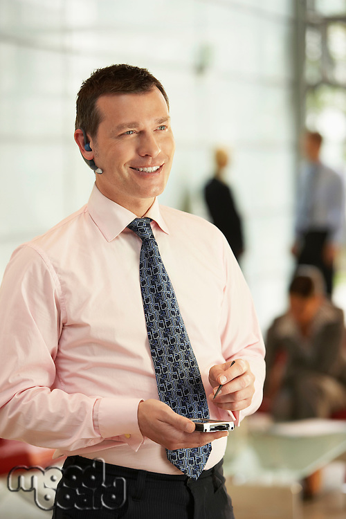 Businessman Using Wireless Headset and PDA in office