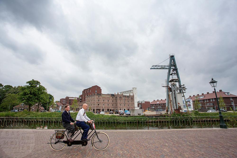 Op een historische tandem rijden twee mannen over de sluis bij de voormalige Cereol fabriek in de wijk Oog in Al. Bij Utrecht wordt de tandemtocht gehouden. De tocht werd van 1975 tot 1982 jaarlijks gehouden en was in die tijd een groots succes. Organisator Herbert Kuner, een expert in oude fietsen, wil het nu nieuw leven inblazen. In totaal rijden dit jaar vijftien tandems mee. Tijdens de route van 40km rondom Utrecht hoeven de fietsers slechts zes verkeerslichten te passeren.<br /> <br /> In Utrecht, the tandem tour is held. The tour was held annually from 1975 to 1982 and at that time was a grand success. Organizer Herbert Kuner, an expert in old bikes, wants to restart the tradition. In total this season, with fifteen tandems. During the route of 40km around and Utrecht cyclists passing only six traffic lights.