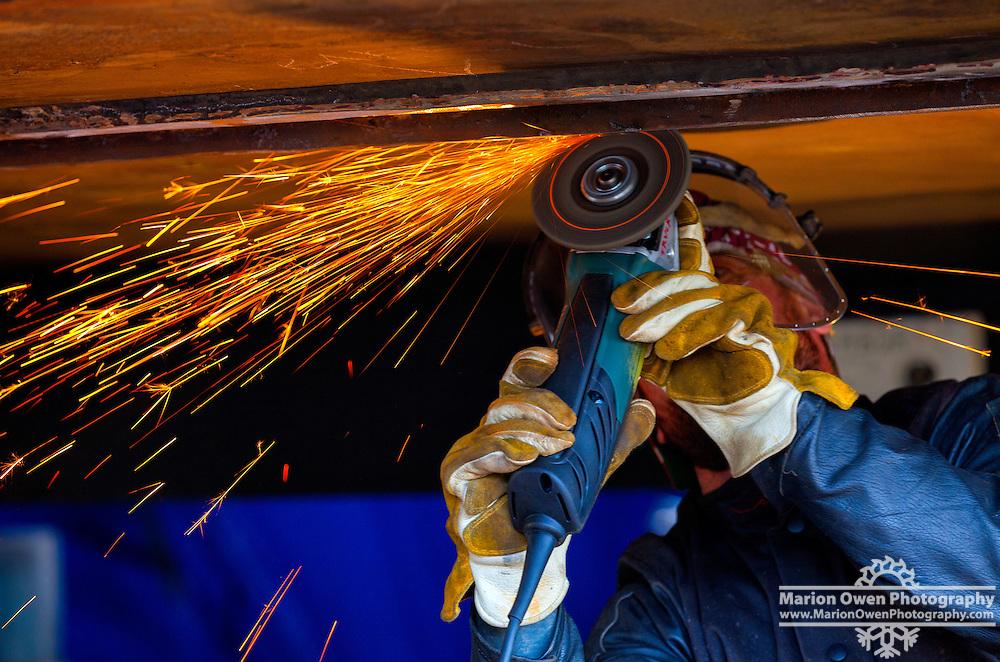 Shipyard worker operates grinder on hull of fishing vessel, in Kodiak, Alaska shipyard.