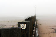 Portobello Beach, Edinburgh in fog. No 2 on wooden seawall.
