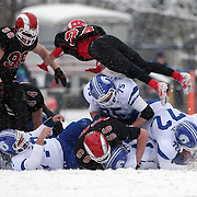 Maxson Wilson, New Canaan, dives over the tackled player during the New Canaan Rams Vs Darien Blue Wave, CIAC Football Championship Class L Final at Boyle Stadium, Stamford. The New Canaan Rams won the match in snowy conditions 44-12. Stamford,  Connecticut, USA. 14th December 2013. Photo Tim Clayton