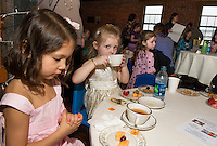 Jocelyn Sprague and Gracie Dube sit and enjoy a cup of tea together during Lakes Region Community Services sponsored Children's Authors Tea at the Belknap Mill Tuesday evening.   (Karen Bobotas/for the Laconia Daily Sun)