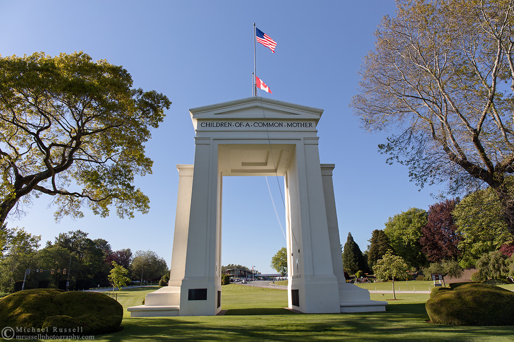 "The Peace Arch (1921) looking towards Canada.  Photographed from Peace Arch Historical State Park in Blaine, Washington State, USA.  The Peace Arch was built in 1921 to commemorate the 100 year anniversary of treaties at the end of the War of 1812 between the USA and Great Britain. One side states ""Children Of A Common Motherr"", the other ""Brethren Dwelling Together In Unity""."