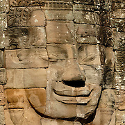 These giant faces carved out of sheer rock loom large against the backdrop of the forest.  <br /> <br /> Angkor Thom (Khmer: អង្គរធំ; literally: &quot;Great City&quot;), located in present day Cambodia, was the last and most enduring capital city of the Khmer empire. It was established in the late twelfth century by King Jayavarman VII. It covers an area of 9 km&sup2;, within which are located several monuments from earlier eras as well as those established by Jayavarman and his successors. At the centre of the city is Jayavarman's state temple, the Bayon, with the other major sites clustered around the Victory Square immediately to the north.<br /> <br /> Angkor Thom was established as the capital of Jayavarman VII's empire, and was the centre of his massive building programme. One inscription found in the city refers to Jayavarman as the groom and the city as his bride.<br /> <br /> Angkor Thom seems not to be the first Khmer capital on the site, however. Yasodharapura, dating from three centuries earlier, was centred slightly further northwest, and Angkor Thom overlapped parts of it. The most notable earlier temples within the city are the former state temple of Baphuon, and Phimeanakas, which was incorporated into the Royal Palace. The Khmers did not draw any clear distinctions between Angkor Thom and Yashodharapura: even in the fourteenth century an inscription used the earlier name. The name of Angkor Thom&mdash;great city&mdash;was in use from the 16th century.<br /> <br /> Faces on Prasat Bayon<br /> The last temple known to have been constructed in Angkor Thom was Mangalartha, which was dedicated in 1295. Thereafter the existing structures continued to be modified from time to time, but any new creations were in perishable materials and have not survived. In the following centuries Angkor Thom remained the capital of a kingdom in decline until it was abandoned some time prior to 1609, when an early western visitor wrote of an uninhabited city, &quot;as fant