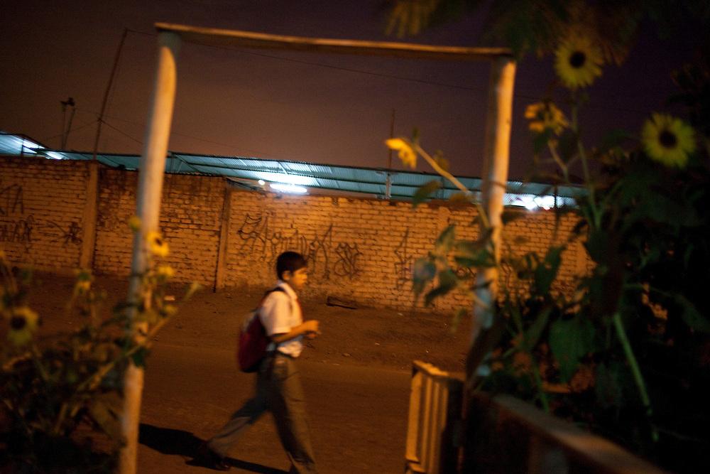 A boy walks down the street on Tuesday, Apr. 7, 2009 in Ventanilla, Peru.