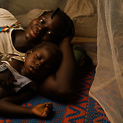 "Mariam Ouedraogo (22) and her daughter, Rachidatu Ouedraogo (3) under the mosquito net they share at their home in the village of Bore in the Sanmatenga region of Burkina Faso on 24 February 2014. Mariam says that since they have had the net she has ""noticed a big difference, because before I couldn't even sleep because of the mosquitos. But now the mosquitos no longer bite me because I sleep under a net."" Mosquito nets greatly decrease the incidence of malaria by reducing the risk of being bitten by the nocturnal Anopheles mosquito, which carries the malaria parasite."