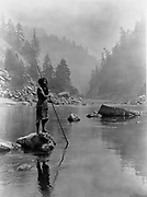 Hupa man with spear, standing on rock midstream, in background, fog partially obscures trees on mountainsides, 1923. Photograph by Edward Curtis (1868-1952).