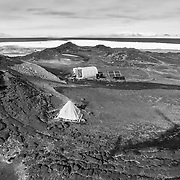 Arriving at Cape Royds Camp. A small setup for two field biologists to study the nearby Adelie Penguin colony. The further tent is a Polar Haven used as a kitchen and social area, powered 100% by solar power. As simple at this staion looks, it was wired for technology. Jean Pennycook, one of the researchers at the camp, was giving live lessons to classrooms around the US from the penguin colony using an ipad and a wireless network set up near the colony.