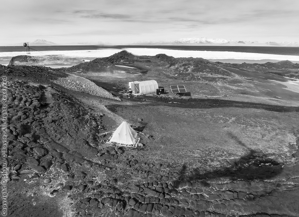Arriving at Cape Royds Camp. A small setup for two field biologists to study the nearby Adelie Penguin colony. The further tent is a Polar Haven used as a kitchen and social area, supplied 100% by solar power. As simple at this staion looks, it was wired for technology. Jean Pennycook, one of the biologist at the camp, was giving live lessons to classrooms around the US from the penguin colony using an ipad and a wireless network set up near the colony.