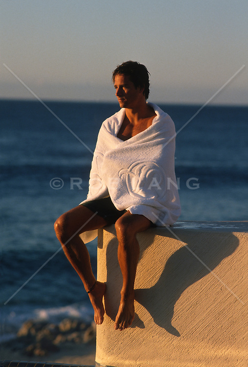 Man by the ocean wrapped in a towel watching a sunset