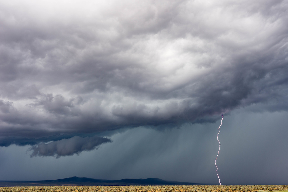 A lightning bolt strikes the ground during a storm outside of Taos, NM