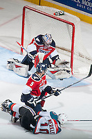 KELOWNA, CANADA - MARCH 27: Nick Merkley #10 of Kelowna Rockets takes a shot on the net of Eric Comrie #1 after being check to the ice by Tyler Morrison #5 of Tri-City Americans on March 27, 2015 at Prospera Place in Kelowna, British Columbia, Canada.  (Photo by Marissa Baecker/Shoot the Breeze)  *** Local Caption *** Tyler Morrison; Eric Comrie; Nick Merkley;