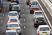 Saloon cars bumper-to-bumper in traffic congestion on M25 motorway, London, United Kingdom