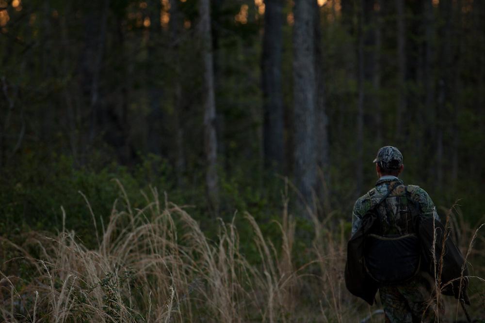 Lone hunter walking through a field.