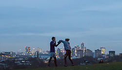 Primrose Hill, London, January 12th 2017. Dawn breaks over London, seen from Primrose Hill, as the South East of England braces itself for rain and possibly snow later in the day. PICTURED: A man and a woman practice their boxing against the backdrop of London's skyscrapers.