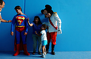 &quot;that's super, man&quot;<br /> <br /> A passerby stops to check the material on Superman's costume, as a family motions to someone else to join them in a photo with Mickey Mouse.  Both the super hero and the icon were on-hand to greet people during the grand opening of the Miami Children's Museum.