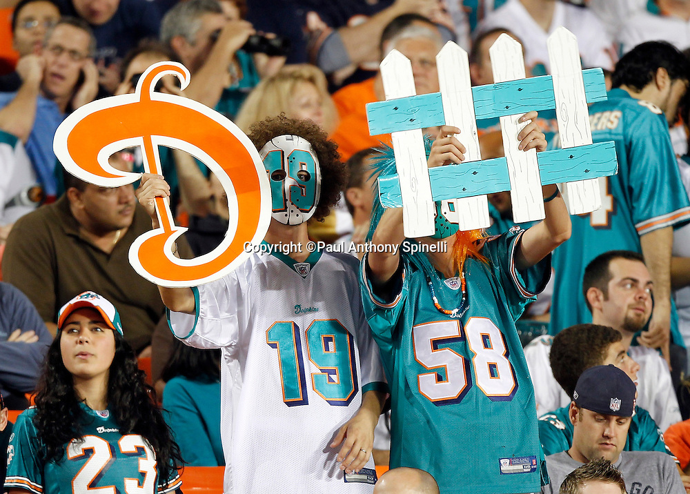 """Miami Dolphins fans hold up a defense """"D fence"""" sign during the NFL week 11 football game against the Chicago Bears on Thursday, November 18, 2010 in Miami Gardens, Florida. The Bears won the game 16-0. (©Paul Anthony Spinelli)"""