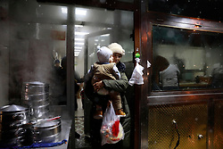 An ethnic Uighur woman carrying her baby walks out of a restaurant in Urumqi city, Xinjiang Uighur Autonomous Province, China, 16 November 2017. Uighurs, a Muslim ethnic minority group in China, make up about 40 per cent of the 21.8 million people in Xinjiang, a vast, ethnically divided region that borders Pakistan, Afghanistan, Kazakhstan, Kyrgyzstan and Mongolia. Other ethnic minorities living in here include the Han Chinese, Kyrgyz, Mongolian and Tajiks people. Xinjiang has long been subjected to separatists unrests and violent terrorist attacks blamed by authorities on Islamist extremism while human rights groups say Chinese repression on religious rights, culture and freedom of movement caused undue tensions. Life however goes on under the watchful eye of the government for the ethnic Uighurs living in the city of Urumqi and surrounding areas and the region is still considered an attractive tourist spot. A recent report by state media Xinhua news agency claims Xinjiang received more than 100 million tourists in 2017, 'the highest figure in its history'.