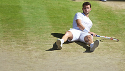 LONDON, ENGLAND - Friday, July 4, 2014: Grigor Dimitrov (BUL) looks dejected after falling over during the Gentlemen's Singles Semi-Final match on day eleven of the Wimbledon Lawn Tennis Championships at the All England Lawn Tennis and Croquet Club. (Pic by David Rawcliffe/Propaganda)