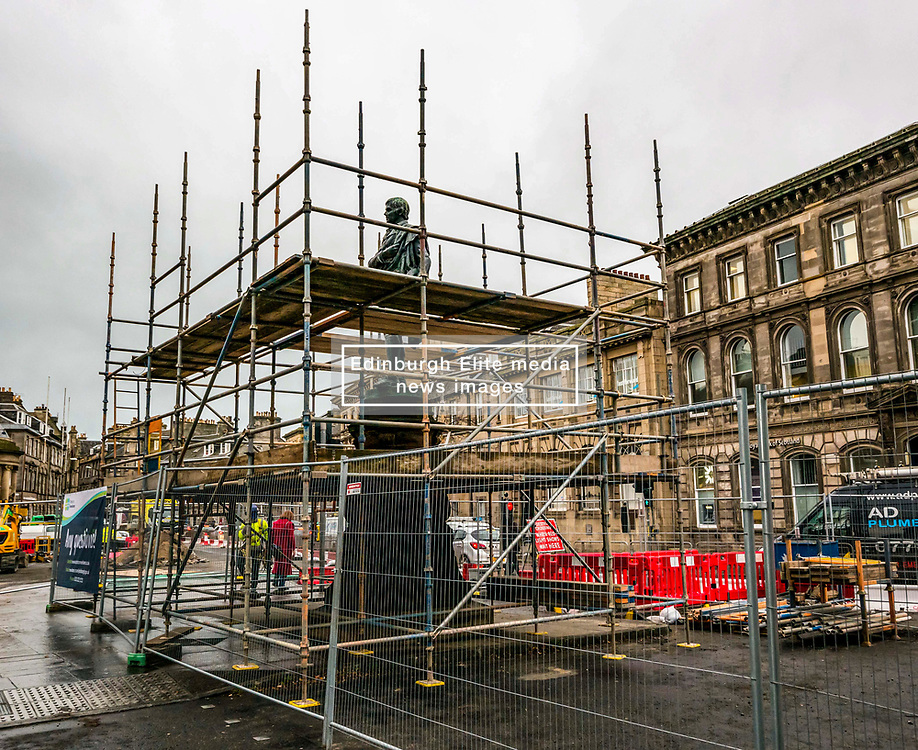 "Edinburgh, Edinburgh, Scotland, United Kingdom, 05 December 2019, Trams to Newhaven: Work is underway in Constitution Street to reroute underground utility pipes and to remove the historic statue of Robert Burns by sculptor D.W. Stevenson RSA erected in 1898 which was cast at the foundry of J.W. Singer and Sons, which is now beiung covered in scaffolding. Banners have been put on the barrier fencing stating ""Any Questions?"",  ""We're supporting local businesses throughout the works"" and ""Thank you for your patience"".  The work is expected to take around 3 years taking the first passengers along the 2.91 mile extension in 2023."