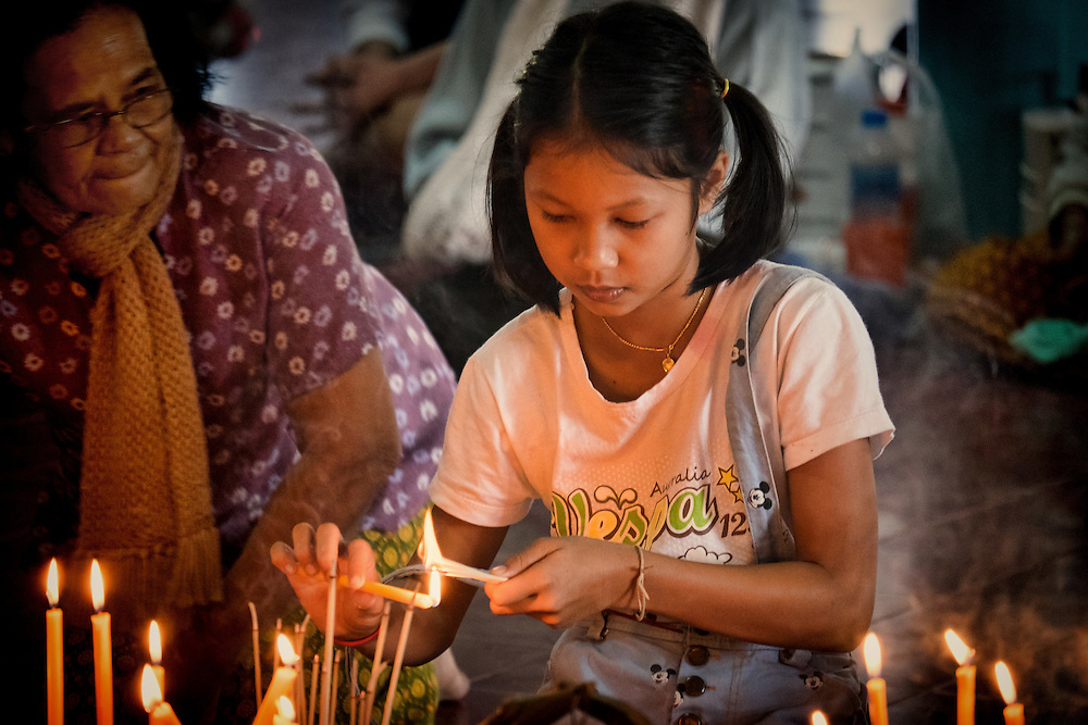 A young woman lights incense as New Years celebrations begin In Nakhon Nayok, Thailand