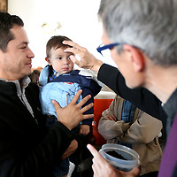 Adam Robison | BUY AT PHOTOS.DJOURNAL.COM<br /> Father Lincoln Dall, from St. James Catholic Church, gives ashes to Emmanuel Alatorre, 1, as he is held by his father Gilberto, during a service held at the West Main Street D' Casa location for the employees Wednesday morning in Tupelo.