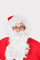 Portrait of man in Santa costume against gray background