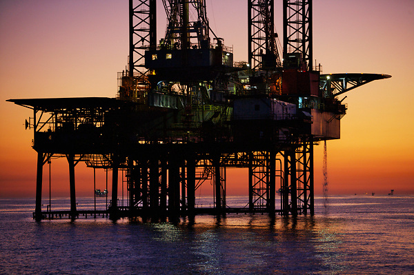 Oil and gas jackup offshore drilling rig with a colorful sunset in the Gulf of Mexico.