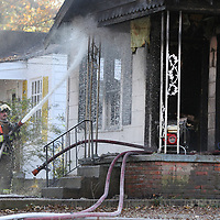 A Tupelo fire fighter soaks down the front porch area at a house fire on the 100 block of South Highland Drive in Tupelo Tuesday afternoon November 27.