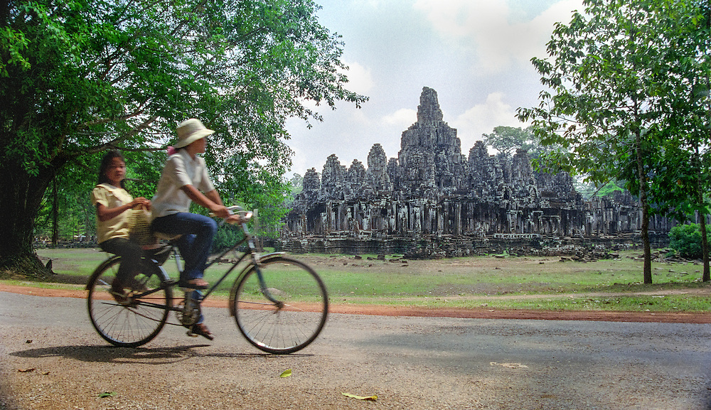 A woman and a young girl on a bicycle near the temple of Bayon, in the ancient city of Angkor, near Siem Reap, Cambodia, 2003.
