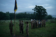 "In this July 28, 2018 photo, young participants and instructors of the ""Temper of will"" summer camp, organized by the nationalist Svoboda party, stand in formation as they sing the national anthem in a village near Ternopil, Ukraine. Earlier this year, the Ministry of Youth and Sports earmarked 4 million hryvnias (about $150,000) to fund some of the youth camps among the dozens built by the nationalists."