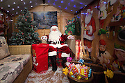 A comical feature showing the diverse and wide variety of Santa Clause's one can find in and around London. Father Christmas seems to have a wide range of appearances and different types of grottos from the elaborate Hamley's Toy Store to a garden shed in a Chobham garden centre. <br /> Pictured - Santa Clause and his grotto at Squire's Garden Centre, Chobham.<br /> Credit: Rick Findler / Story Picture Agency