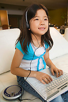 Girl Using Laptop and Listening to Music