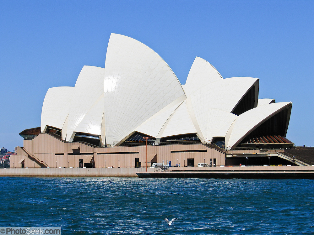 """Sydney Opera House was opened in 1973 on Bennelong Point in Sydney Harbour, Sydney, New South Wales (NSW), Australia. It was conceived and largely built by Danish architect Jørn Utzon after a long gestation starting with his competition-winning design in 1957. Utzon received the Pritzker Prize, architecture's highest honor, in 2003: """"There is no doubt that the Sydney Opera House is his masterpiece… one of the great iconic buildings of the 20th century, an image of great beauty that has become known throughout the world – a symbol for not only a city, but a whole country and continent."""" The Sydney Opera House was honored as a UNESCO World Heritage Site in 2007."""