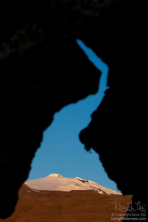 "Snæfellsjökull, a 1,446 meter (4,744 foot) stratovolcano, is framed by a natural arch in a lava field in western Iceland. The volcano, which is active, last erupted approximately 1,800 years ago, creating lava fields at its base. The mountain is technically named Snæfell; Snæfellsjökull is the name of the glacier at its peak. It is commonly called Snæfellsjökull, however, to avoid confusing it with several other mountains with the same name. Snæfellsjökull means ""snow glacier mountain,"" and it was featured in the 1864 novel ""A Journey to the Center of the Earth"" by Jules Verne.."