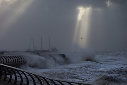 "© Licensed to London News Pictures . 10/12/2014 . Blackpool , UK . The sun breaks through clouds as seen from Blackpool Promenade whilst waves crash in to the seafront . An explosive cyclogenesis - a fast developing storm in which air pressure falls rapidly - known as a "" weather bomb "" - hits the North of England , bringing storms to the region . Photo credit : Joel Goodman/LNP"