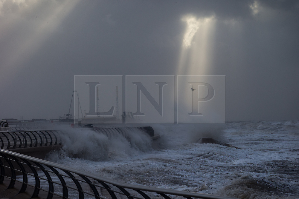 """© Licensed to London News Pictures . 10/12/2014 . Blackpool , UK . The sun breaks through clouds as seen from Blackpool Promenade whilst waves crash in to the seafront . An explosive cyclogenesis - a fast developing storm in which air pressure falls rapidly - known as a """" weather bomb """" - hits the North of England , bringing storms to the region . Photo credit : Joel Goodman/LNP"""