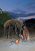 Hadzabe woman in front of her simple hut.