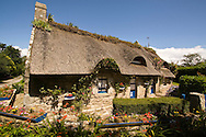 Thatched cottage made with a wall of granite stones