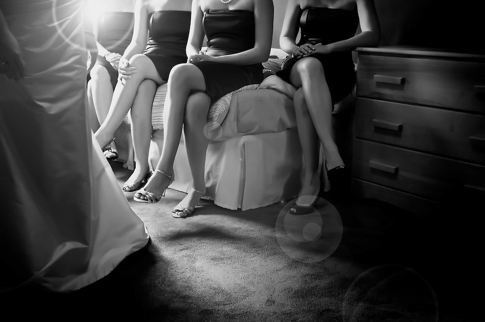 Clasped hands and crossed legs as the bridesmaids watch the bride adorning her wedding gown.