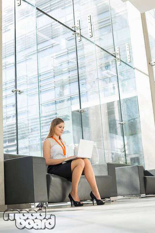 Young businesswoman using laptop at office lobby