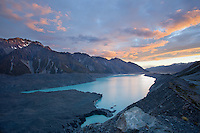 Just below Mount Cook, evening light dominates the sky and illuminates a small lake created by the melting Tasman Glacier. This lake eventually flows into what is the headwaters of Lake Pukaki. In the distance the peaks of The Nun's Veil are painted in light. Mount Cook region of New Zealand.