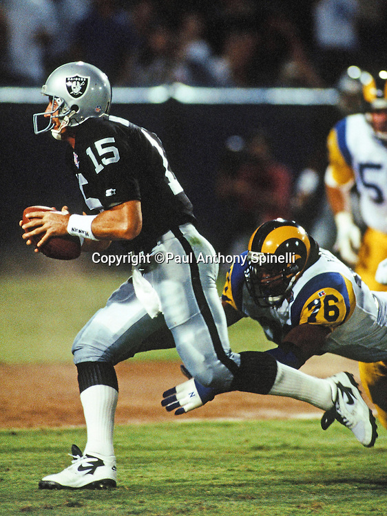 Los Angeles Raiders quarterback Jeff Hostetler (15) runs away from a diving tackle attempt by Los Angeles Rams defensive end Robert Young (76) during the NFL preseason football game against the Los Angeles Rams on Aug. 20, 1994 in Anaheim, Calif. The Raiders won the game 29-20. (©Paul Anthony Spinelli)