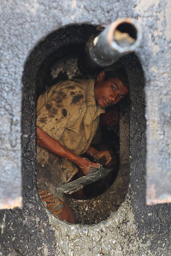 Two workers removing some mix of mud and fuel residues in a ship part, using a shovel as much as their hand.