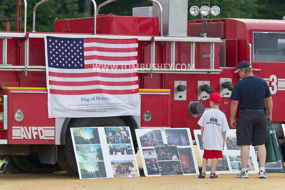 Scotchtown, New York - A man and a boy look a 9/11 display on a fire truck during a Night Out Against Crime event on on Aug. 7, 2012.