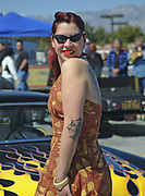 A Rockabilly girl posing in front of a Hotrod car, Viva Las Vegas Festival, Las Vegas, USA 2006.