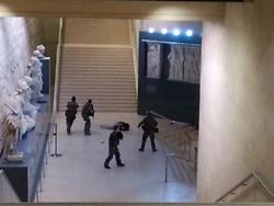 February 3, 2017 - Paris, France -  Le Louvre Attacked by Lone Assailant Yielding Machete. This  photo was taken by a travel guide with a group of 34 Chinese tourists, while they were descending towards the Carrousel of the Louvre Museum Paris and came upon law enforcement after they had stopped the assilant. The four soldiers with weapons drawn, surrounded ABDULLAH EH, 29 (Egyptian), who is on the ground. A French soldier on duty opened fire on Friday, at him after he tried to attack him with a knife at the entry of the Le Louvre Museum. (Credit Image: © Xinhua via ZUMA Wire)