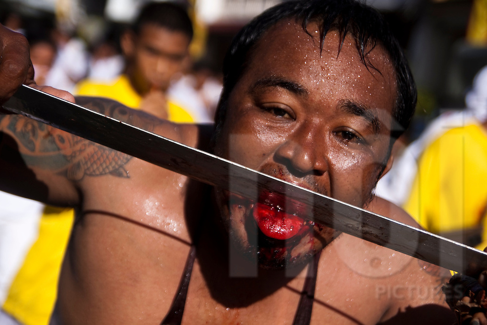 A mah-song licks a sword during the morning procession at the Phuket Vegetarian Festival, Phuket, Thailand.